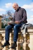 Sirva sentarse leyendo un periódico en una pared de piedra foto de archivo