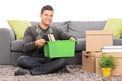 Sirva sentarse por un sofá con las cajas móviles alrededor de él Fotografía de archivo