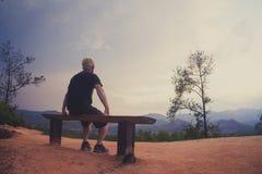 Sirva sentarse solamente en el banco que mira paisaje fotografía de archivo libre de regalías