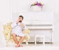Sirva soñoliento en la albornoz, bostezando, café de las bebidas en hotel de lujo por la mañana, fondo blanco Hombre con la barba foto de archivo