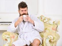 Sirva soñoliento en la albornoz, café de las bebidas, disfrutando del aroma en hotel de lujo por mañana, el fondo blanco Hombre c fotografía de archivo libre de regalías