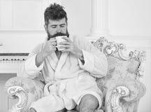 Sirva soñoliento en la albornoz, café de las bebidas, disfrutando del aroma en hotel de lujo por mañana, el fondo blanco Hombre c foto de archivo libre de regalías