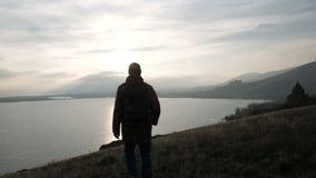 Sirva solamente caminar en la colina al mar en la puesta del sol