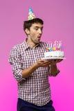 Sirva soplar hacia fuera velas en la torta de cumpleaños sobre fondo púrpura Imagen de archivo