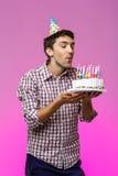 Sirva soplar hacia fuera velas en la torta de cumpleaños sobre fondo púrpura Imagen de archivo libre de regalías