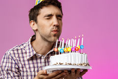 Sirva soplar hacia fuera velas en la torta de cumpleaños sobre fondo púrpura Fotografía de archivo libre de regalías