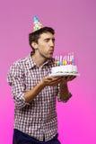 Sirva soplar hacia fuera velas en la torta de cumpleaños sobre fondo púrpura Fotografía de archivo