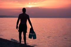 Sirva sostener aletas del tubo respirador en la playa en la puesta del sol Fotografía de archivo libre de regalías