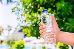 Sirva sostener el agua claramente potable en una botella plástica en fondo borroso verano Foto de archivo libre de regalías