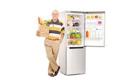 Sirva sostener el bolso con los ultramarinos por un refrigerador abierto Fotografía de archivo libre de regalías