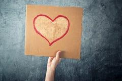 Sirva sostener el papel de la cartulina con el dibujo de la forma del corazón Fotografía de archivo