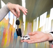 Sirva sostener el pequeño coche, mujer que lleva a cabo llave del coche Foto de archivo libre de regalías