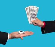 Sirva sostener el pequeño coche, otro hombre que lleva a cabo billetes de dólar Foto de archivo