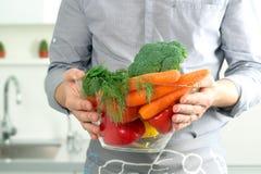 Sirva sostener el plato de cristal con las verduras frescas en la cocina Fotos de archivo libres de regalías