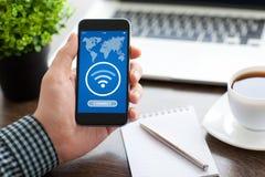 Sirva sostener el teléfono con el uso para buscar gratis Wi-Fi Imagen de archivo libre de regalías