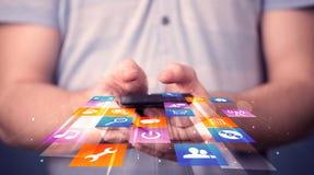 Sirva sostener el teléfono elegante con los iconos coloridos del uso Imagenes de archivo
