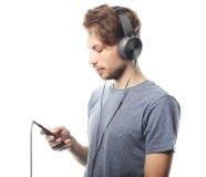 Sirva sostener el teléfono móvil y lictening a la música sobre el backg blanco Fotografía de archivo libre de regalías
