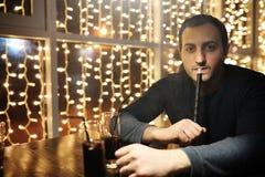 Sirva sostener el tubo de la cachimba y fumar en un club de noche Fotos de archivo libres de regalías