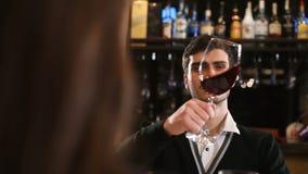 Sirva sostener el vino rojo en vidrio y la sacudida para probar Compruebe la calidad del vino rojo almacen de metraje de vídeo