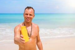 Sirva sostener la botella amarilla de la protección solar en la playa imagenes de archivo