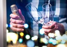 Sirva sostener la botella del champán o vino espumoso y dos vidrios fotografía de archivo