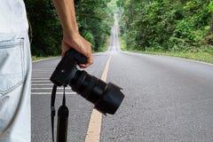 Sirva sostener la cámara digital del dslr en el camino recto borroso en fondo del parque nacional fotos de archivo