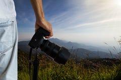 Sirva sostener la cámara digital del dslr en prado borroso y fondo de niebla de la montaña fotos de archivo