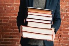 Sirva sostener la pila de libros en manos, primer Foto de archivo