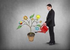 Sirva sostener la regadera y el dibujo de los gráficos de negocio en ramas de la planta en la pared Fotografía de archivo libre de regalías