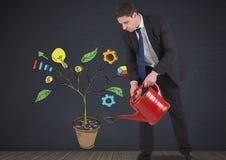 Sirva sostener la regadera y el dibujo de los gráficos de negocio en ramas de la planta en la pared Foto de archivo
