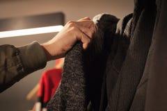 Sirva sostener la ropa en una tienda durante compras fotos de archivo