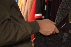 Sirva sostener la ropa en una tienda durante compras imagenes de archivo