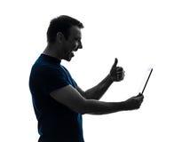 Sirva sostener la silueta para arriba satisfecha digital del pulgar de la tableta Imágenes de archivo libres de regalías