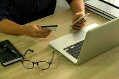 Sirva sostener la tarjeta de crédito y usar el smartphone para las compras del pago foto de archivo libre de regalías