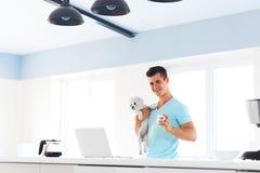 Sirva sostener su perro, colocándose con una taza de café en el kitche Foto de archivo libre de regalías