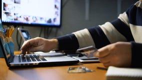 Sirva sostener tarjetas de un crédito y usar el ordenador portátil para las compras en línea almacen de metraje de vídeo