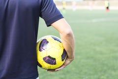 Sirva sostener un balón de fútbol en el campo Imagen de archivo libre de regalías