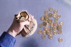 Sirva sostener un bolso del dinero lleno de dólares Foto de archivo