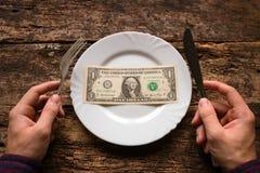 Sirva sostener un cuchillo y una bifurcación al lado de la placa que es un dólar Imágenes de archivo libres de regalías