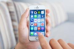 Sirva sostener un iPhone blanco 5s con medios programa social de la red Foto de archivo