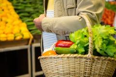 Sirva sostener una cesta de verduras en mercado estupendo imágenes de archivo libres de regalías