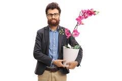 Sirva sostener una flor de la orquídea en un pote Fotografía de archivo