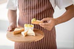 Sirva sostener una placa de tostadas con la miel y el queso Imagenes de archivo