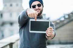 Sirva sostener una tableta y señalar en la pantalla - fondo borroso Imagenes de archivo
