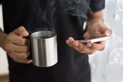 Sirva sostener una taza de café mientras que usa smartphone en su hogar Imágenes de archivo libres de regalías