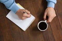 Sirva sostener una taza de café y la escritura en la libreta Imagen de archivo libre de regalías