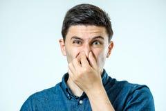 Sirva sostenerse la nariz contra un mún olor imagenes de archivo