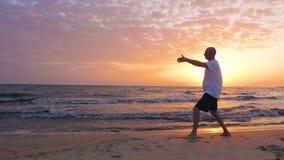 Sirva a Tai Chi de entrenamiento chuan mientras que salida del sol de la mañana en cielo en la playa del mar metrajes