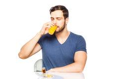 Sirva tener en píldoras y zumo de naranja delanteros Fotografía de archivo
