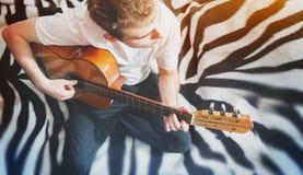 Sirva tocar la guitarra en casa, sonrisa, sentándose en cama Foto de archivo libre de regalías